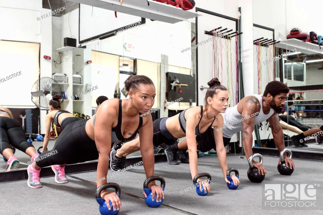Stock Photo: Man and women doing push-ups with kettlebells.