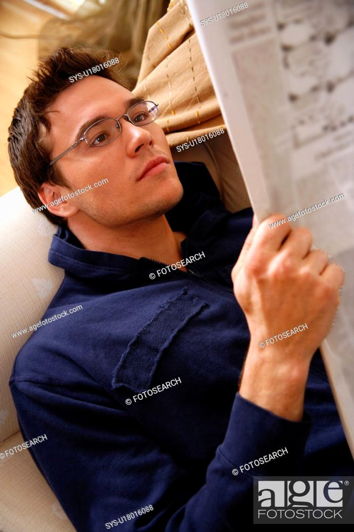 Stock Photo: Young man reading a newspaper.