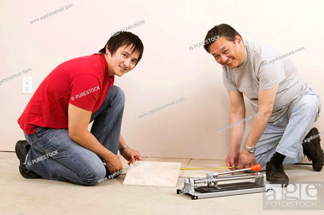 Stock Photo: Side profile of a mid adult man and a young man measuring a tile with a tape measure.