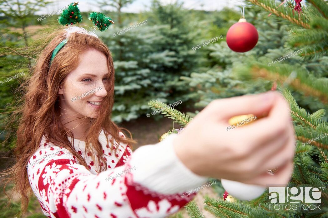 Imagen: Redheaded young woman decorating Christmas tree outdoors.