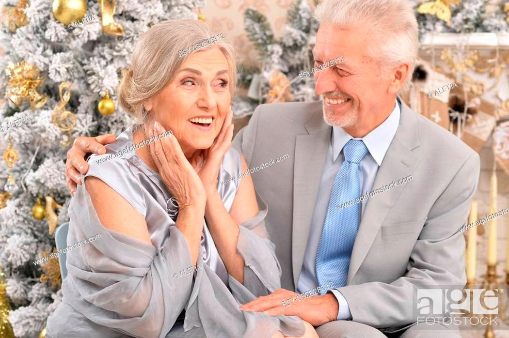 Stock Photo: Portrait of elegant elderly couple near christmas tree.
