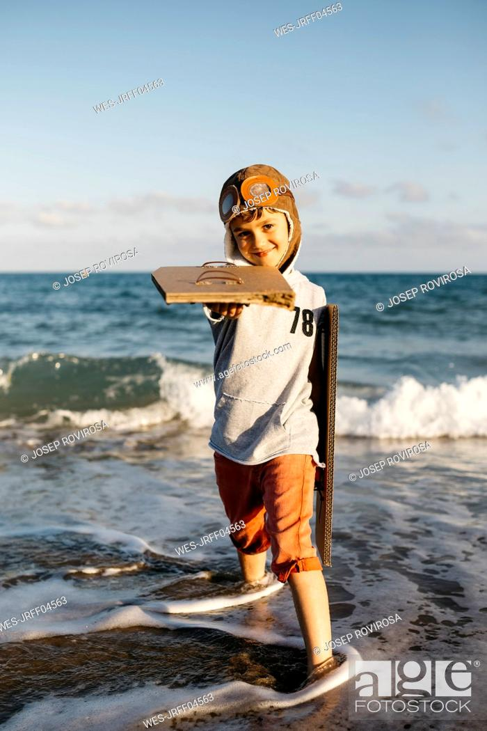 Stock Photo: Boy with aviator's cap holding cardboard wings while standing at beach.