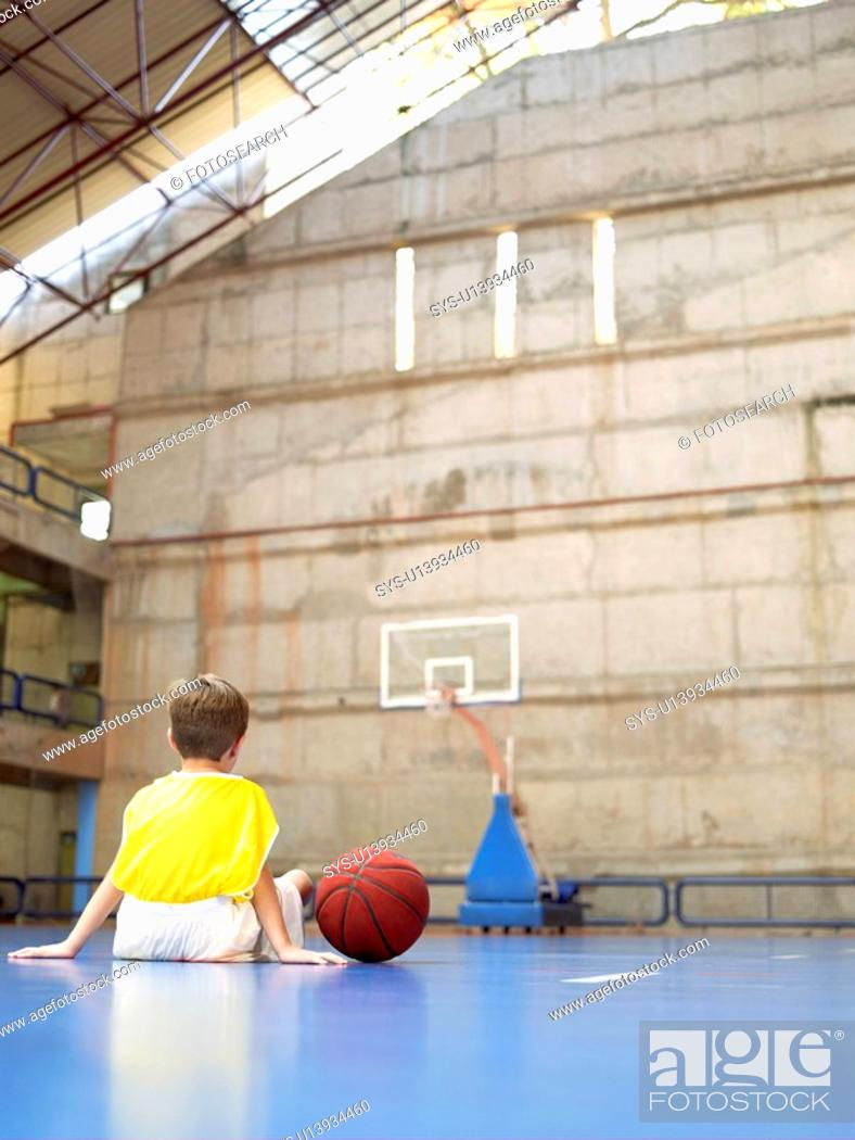 Stock Photo: Boy sitting in basketball court rear view.