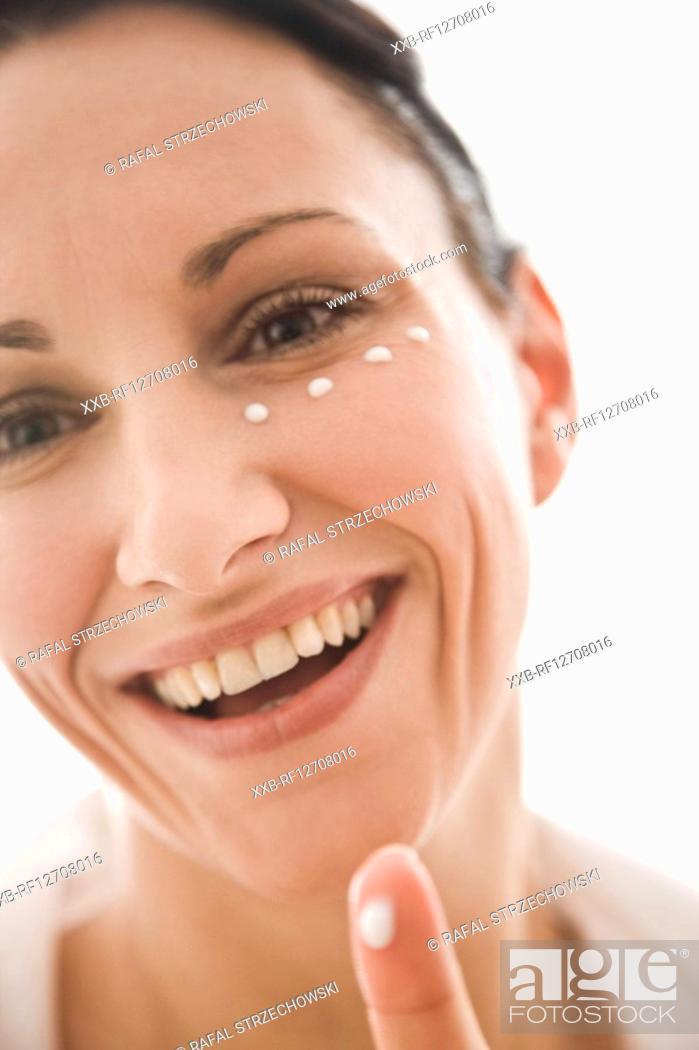 Stock Photo: woman applying eye cream.