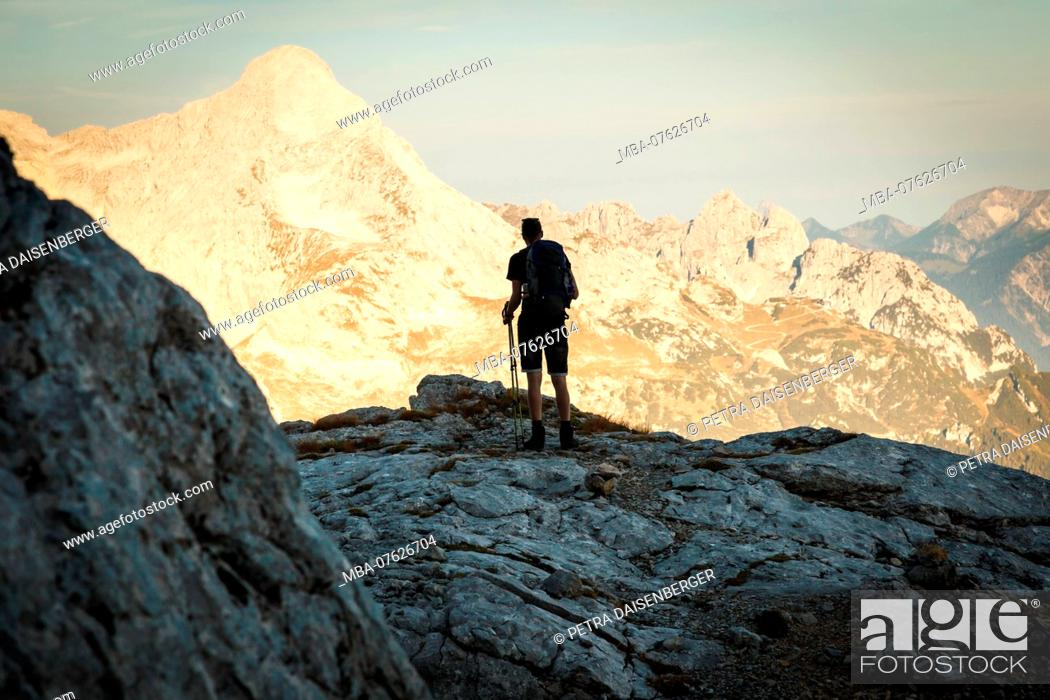 Imagen: A young man on a mountain hike in the Wetterstein, enjoying the view on the Zugspitze and the mountains in Garmisch-Partenkirchen, Bavaria, Germany,.