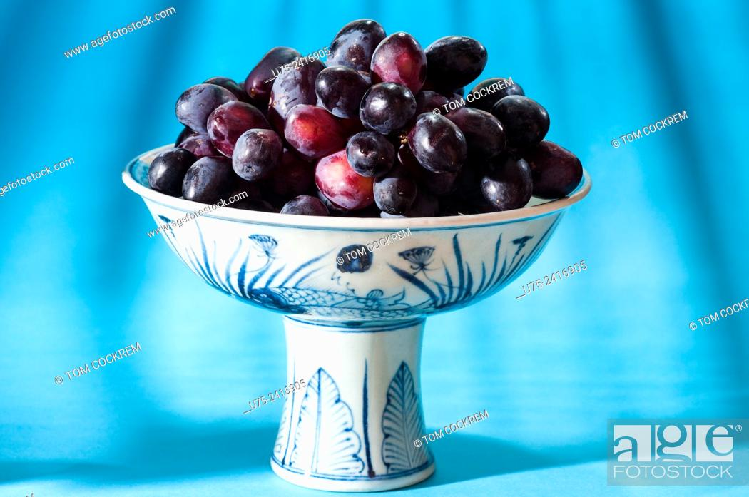 Stock Photo: Ming Dynasty Chinese bowl of black grapes in studio setting.