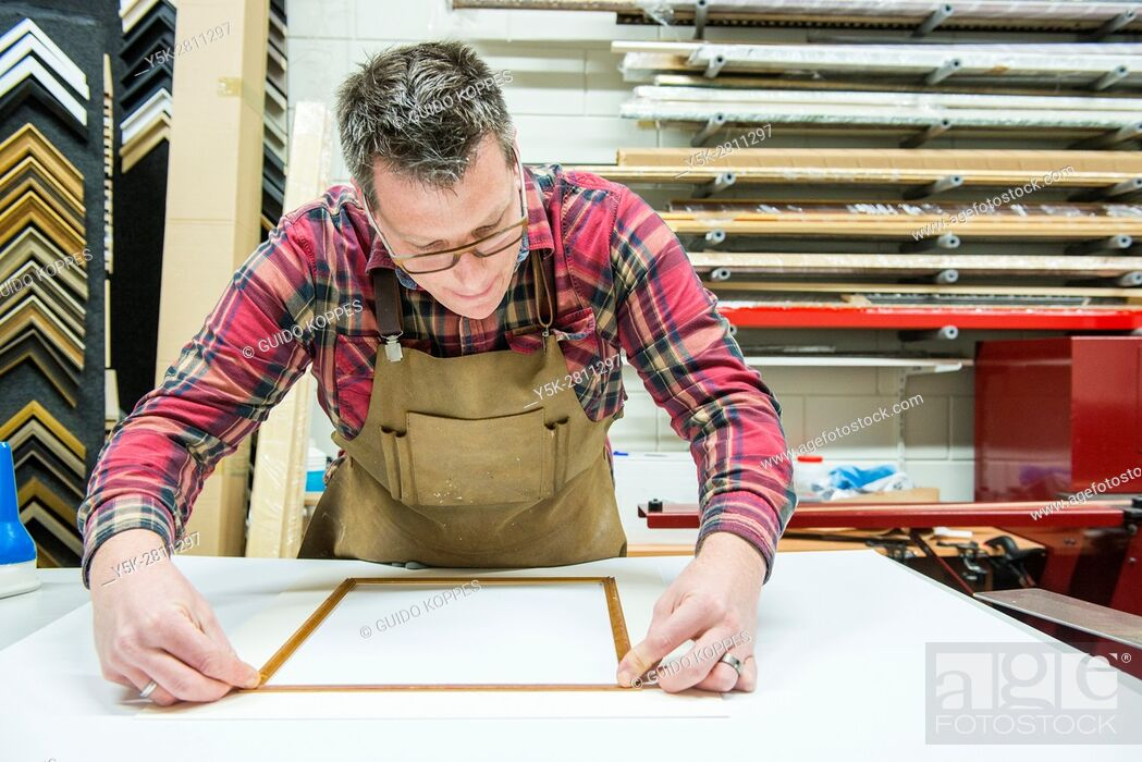 Photo de stock: Goirle, Netherlands. Mid adult male craftsman and picture framemaker working on an assignment for a custiomer inside his workshop.