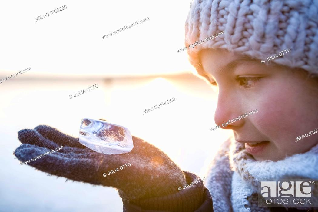 Stock Photo: Germany, Brandenburg, Lake Straussee, portrait of a girl standing on frozen lake, looking at piece of ice on her hand.