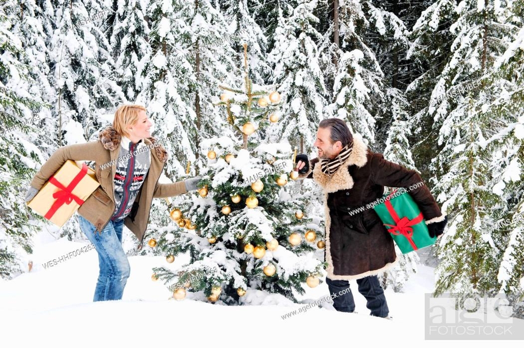 Stock Photo: Austria, Salzburg County, Couple holding christmas gift in snow, smiling.
