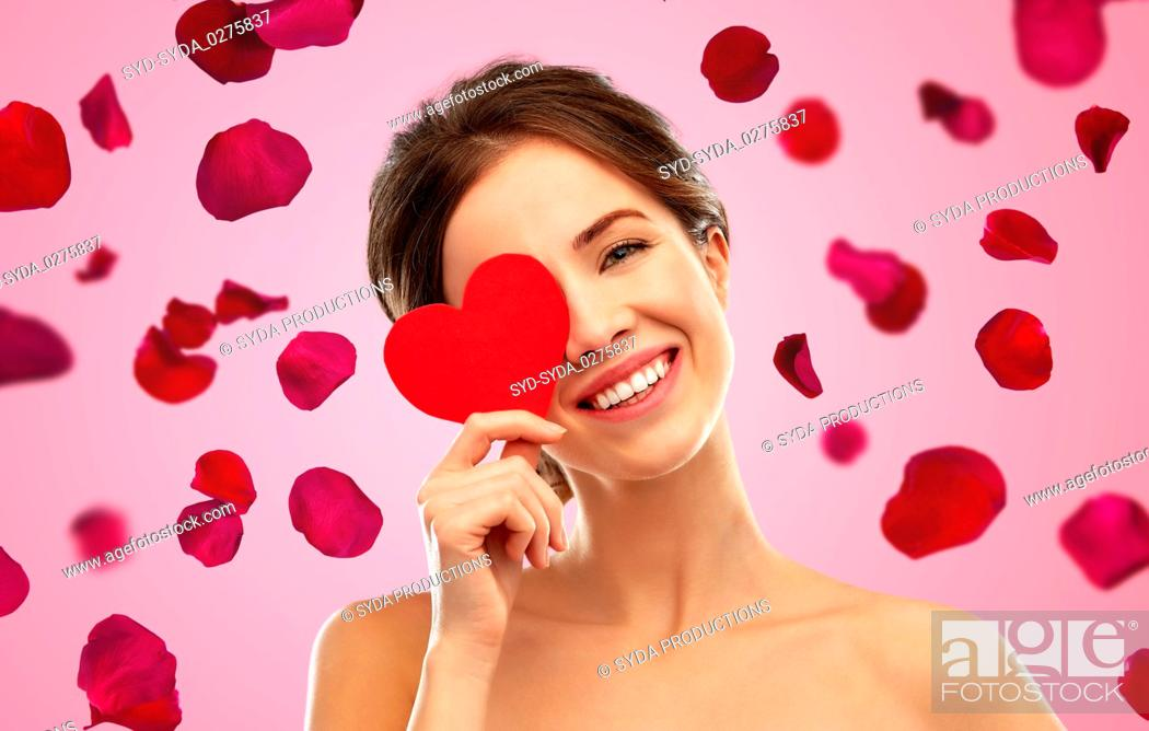 Stock Photo: beautiful smiling woman holding red heart.