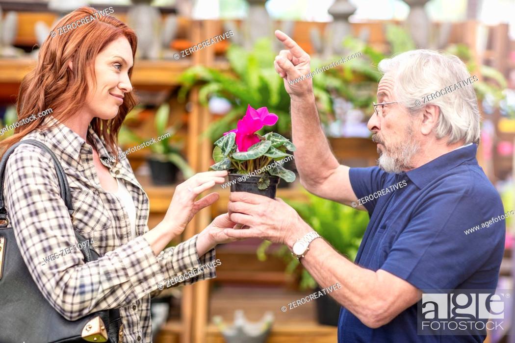 Stock Photo: Gardener helping woman at garden centre.