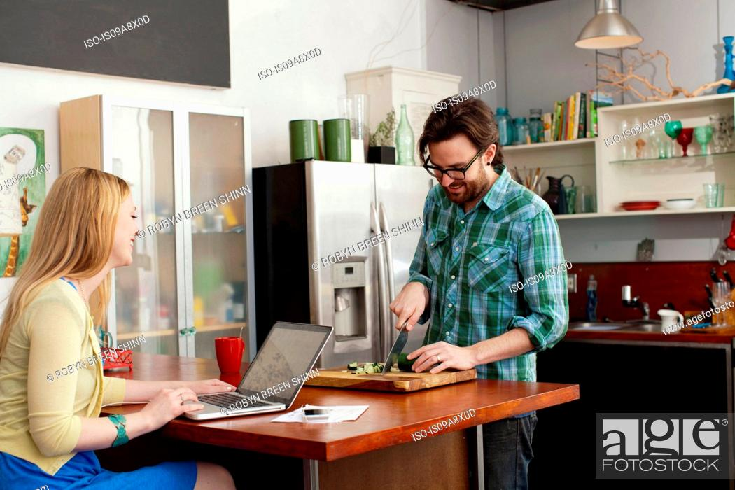 Stock Photo: Woman on laptop computer, man chopping vegetables.