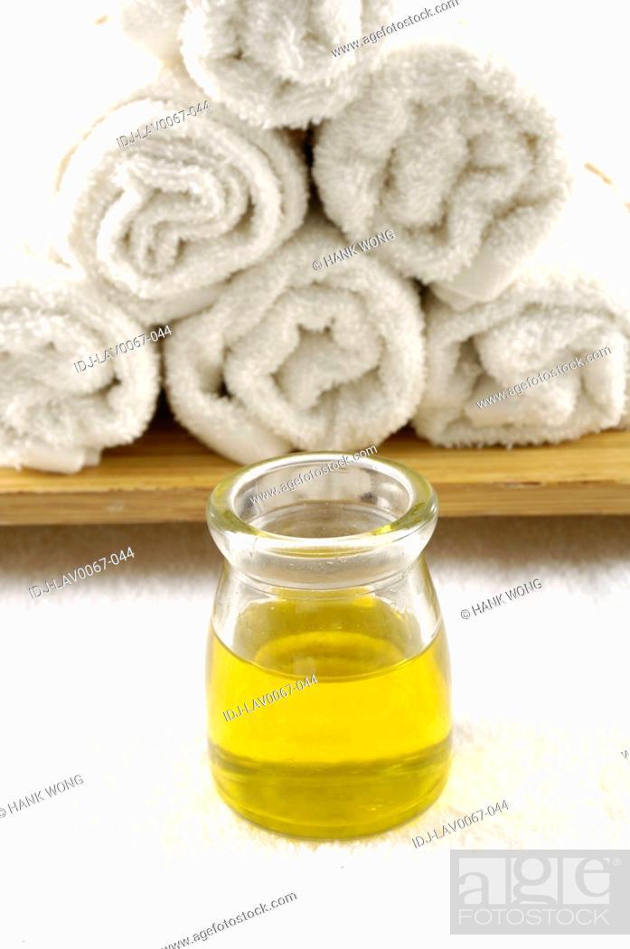 Stock Photo: Massage oil bottle near rolled towels.