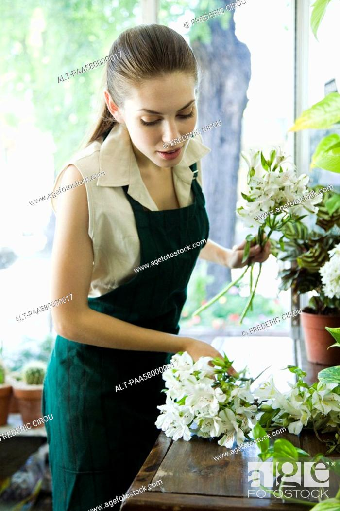 Stock Photo: Female florist arranging flowers in shop.
