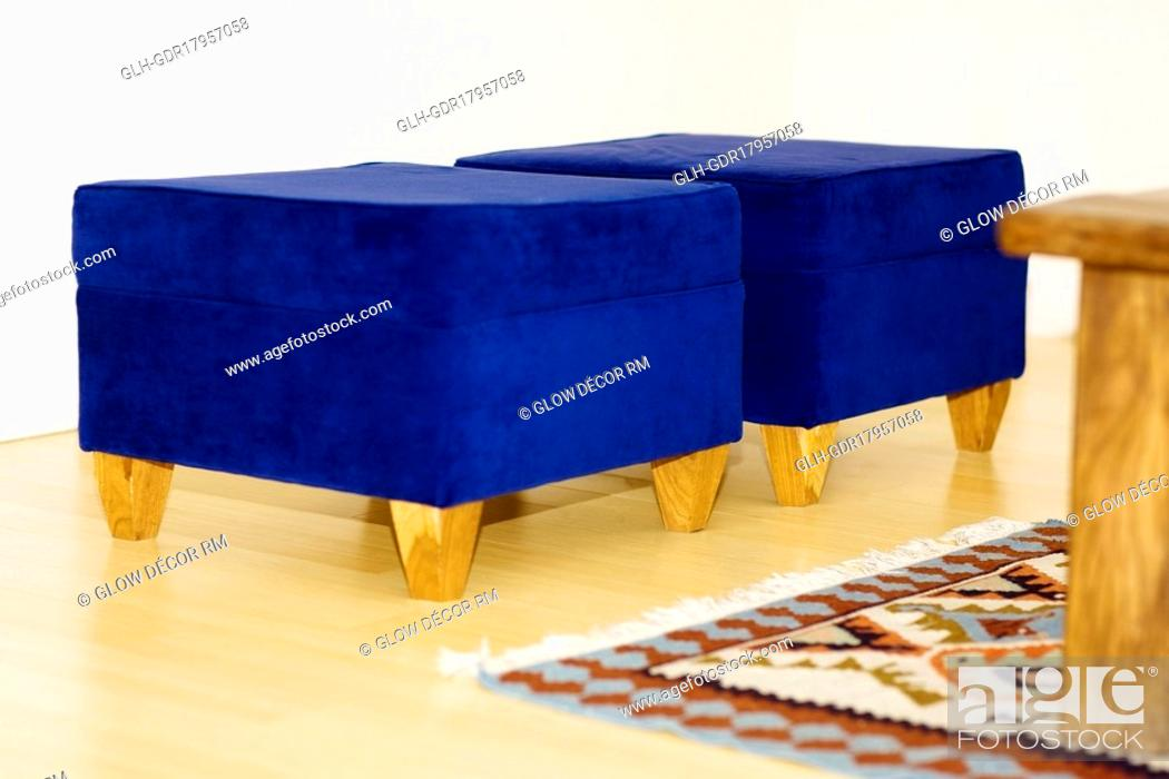 Stock Photo: Two blue ottomans in a living room.