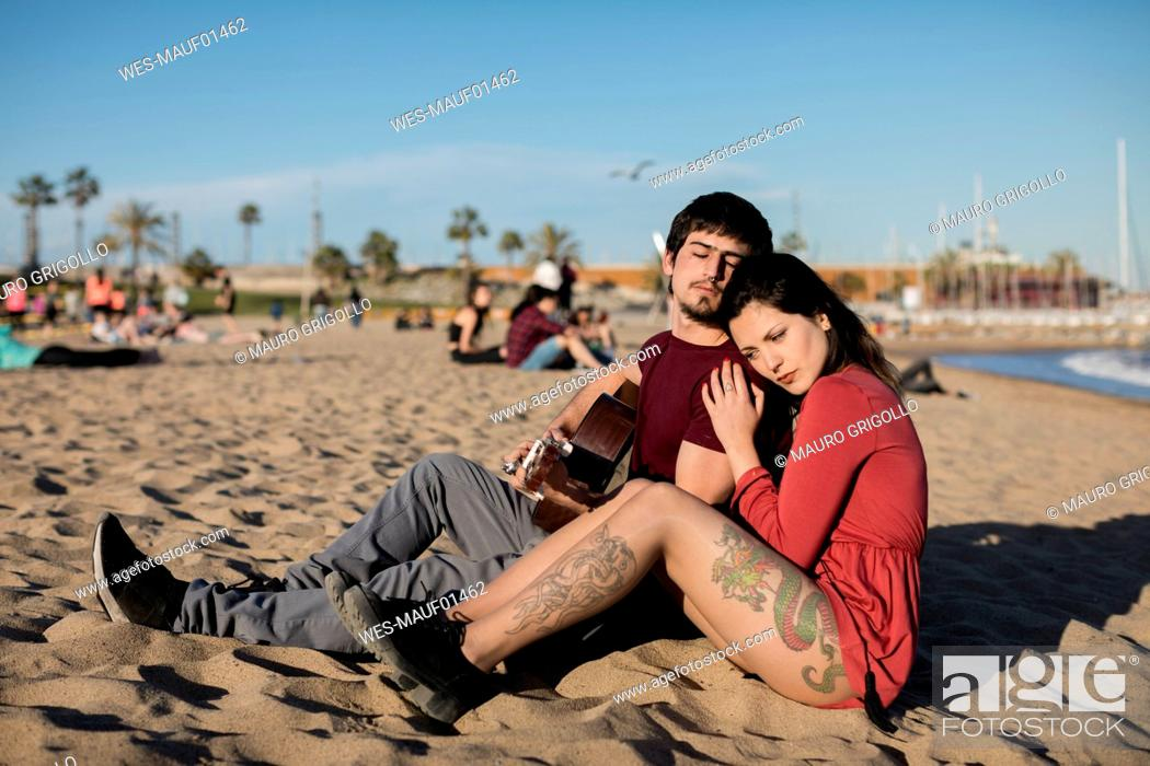 Imagen: Spain, Barcelona, couple with a guitar sitting on the beach.