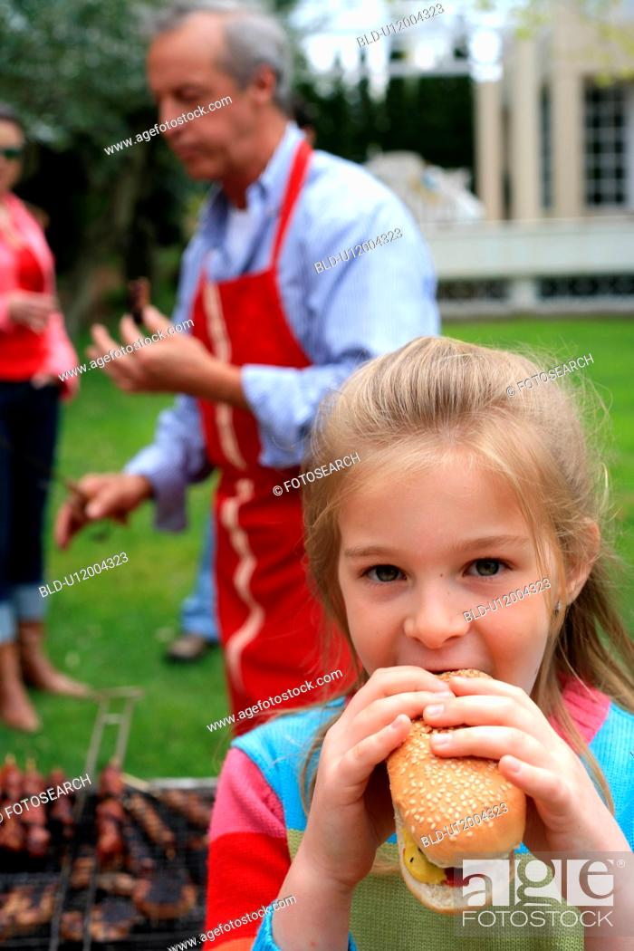 Stock Photo: Young girl eating a hot dog.