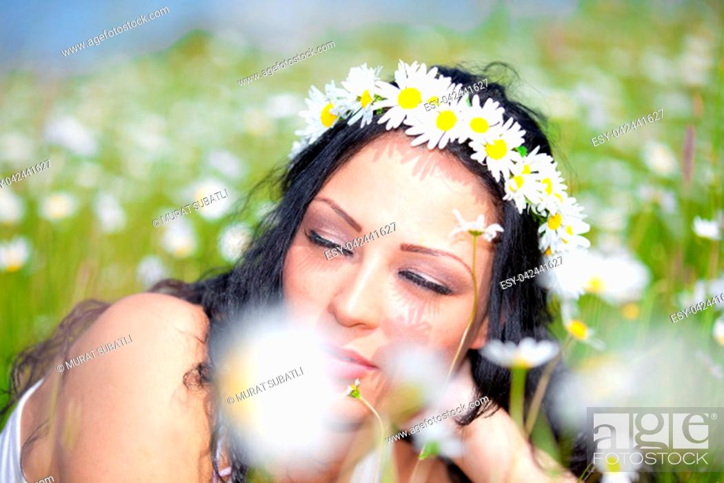 Stock Photo: Beautiful woman laying on the flower filed.