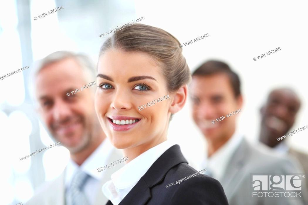 Stock Photo: Blur image of a cheerful business woman in front with her staff standing behind.