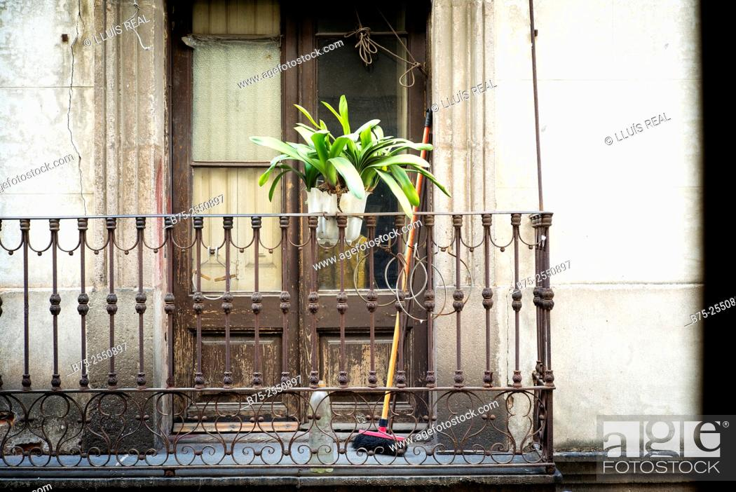 Stock Photo: Balcony with a lower plant and a broom from a house in old town in Barcelona, Spain, Europe.