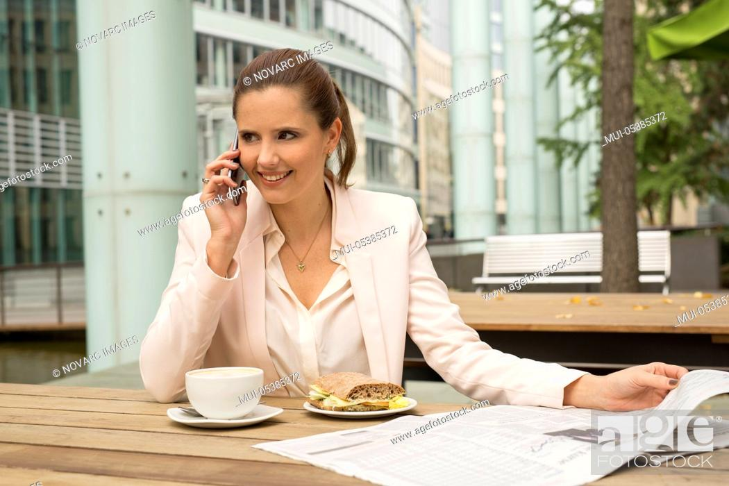 Stock Photo: Young businesswoman sitting in a cafe.