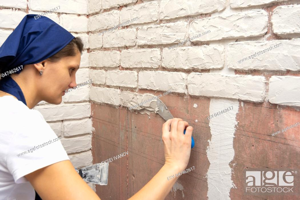 Stock Photo: Plasterer girl makes designer author's imitation of brickwork on the wall of an apartment.