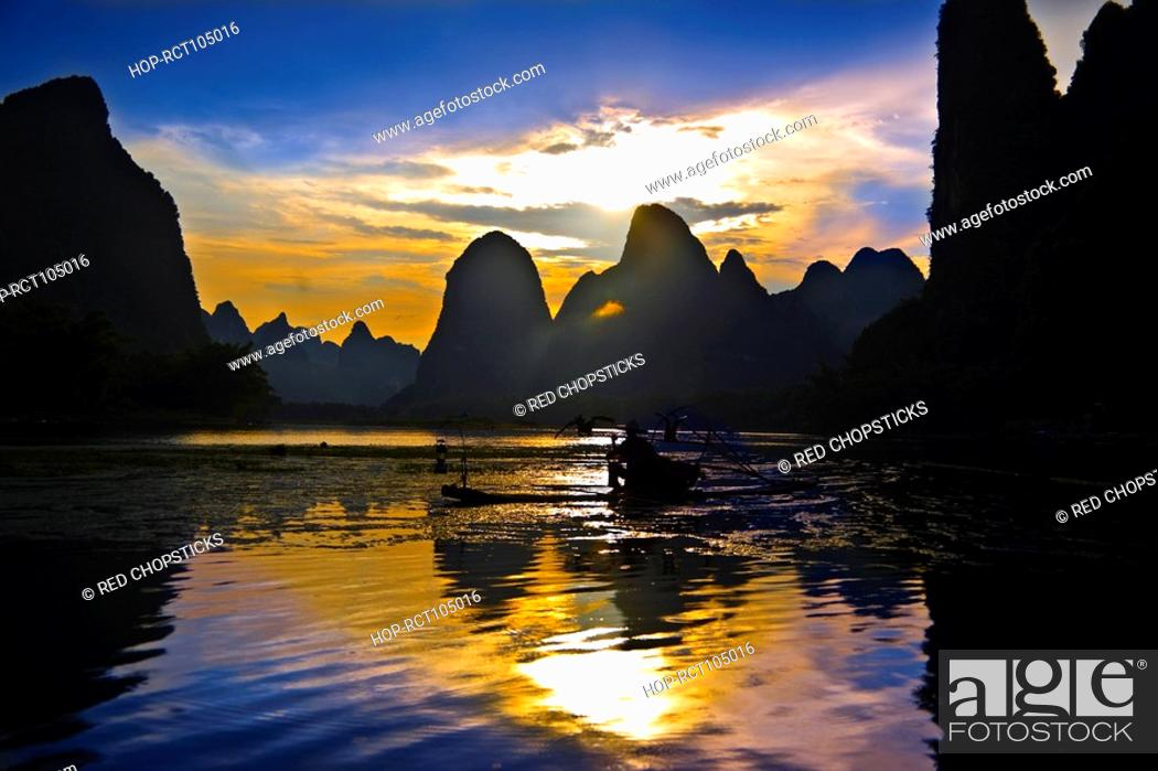 Stock Photo: Fisherman fishing in a river with a hill range in the background, Guilin Hills, XingPing, Yangshuo, Guangxi Province, China.