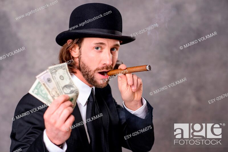 Stock Photo: young businessman with bowler hat and big cigar and money.