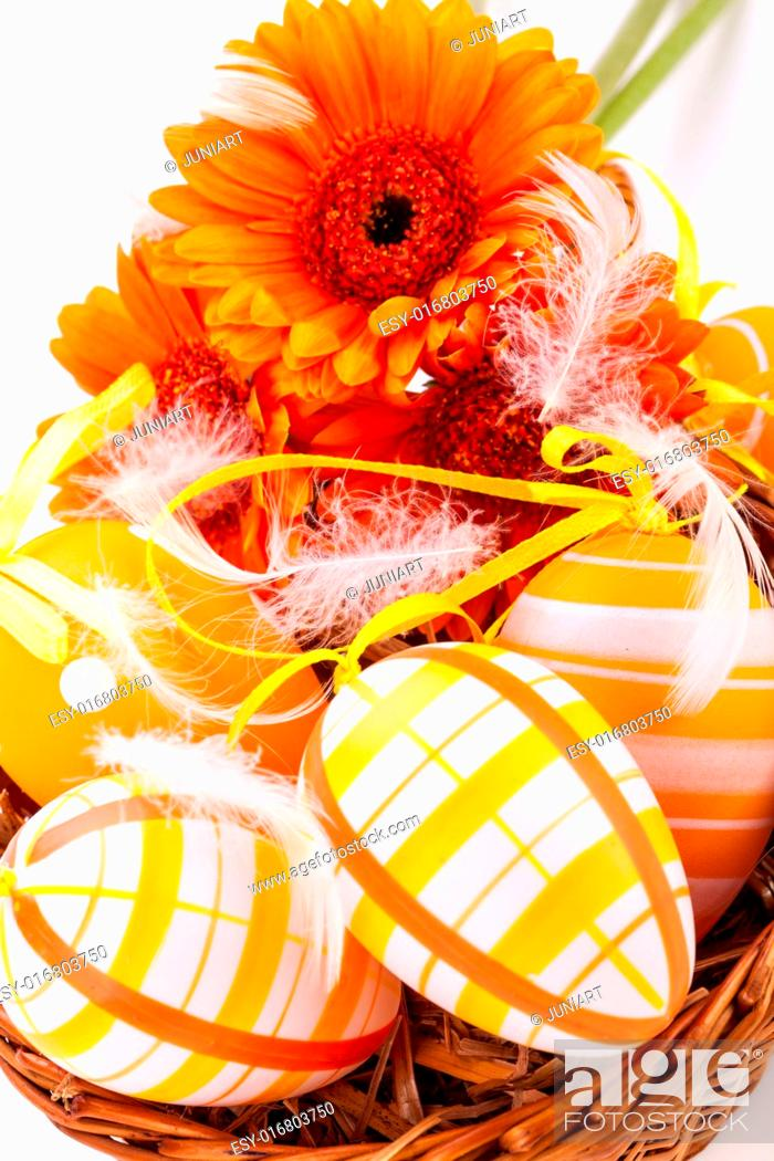 Stock Photo: Colourful yellow hand decorated traditional Easter eggs with stripes and polka dot patterns arranged with colourful orange Gerbera daisies a decorative ribbon.