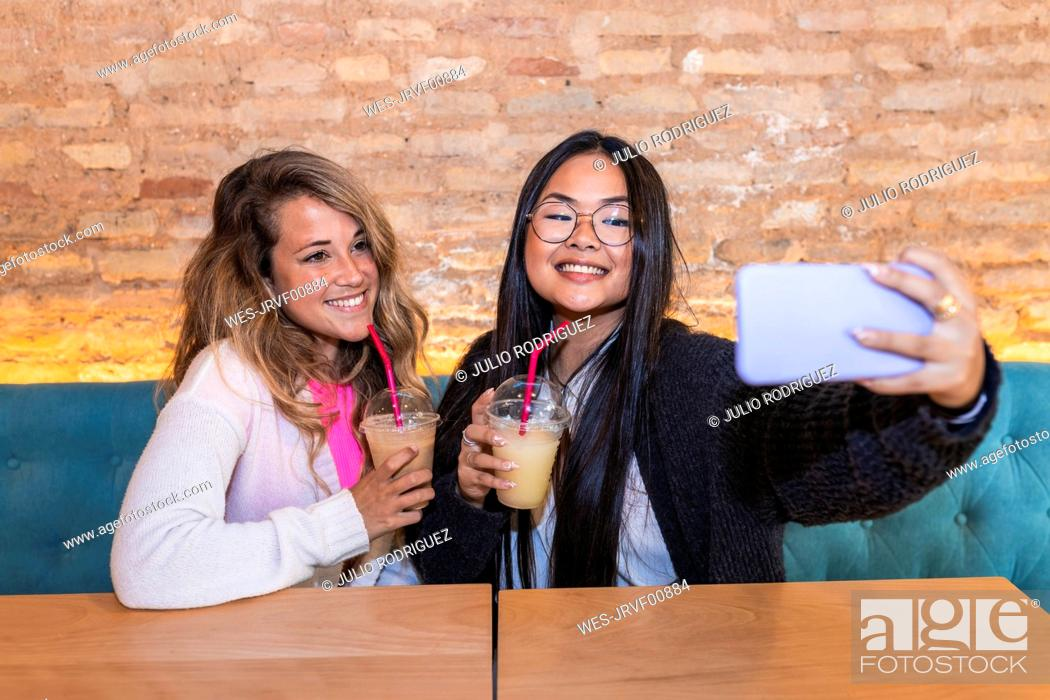 Stock Photo: Young woman taking selfie with female friend through mobile phone in bar.