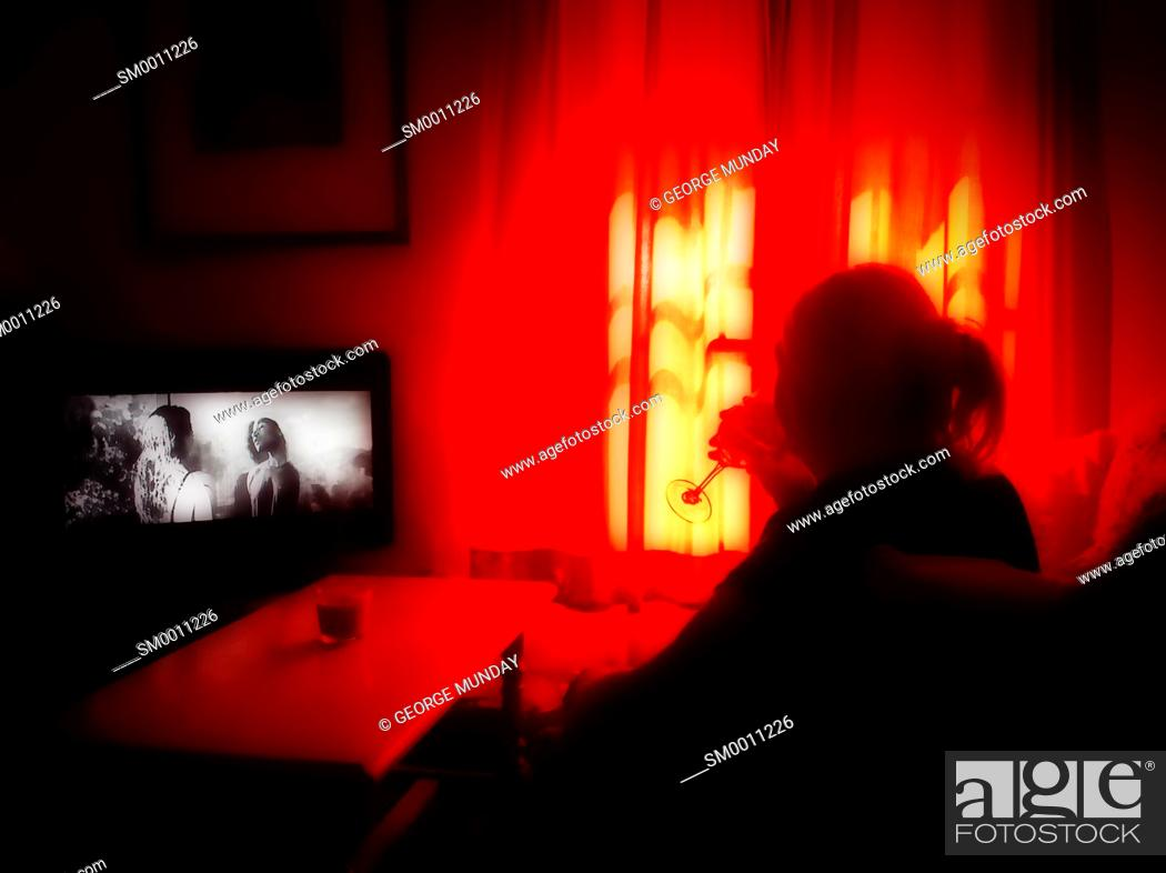 Stock Photo: Woman watching television and drinking wine,.