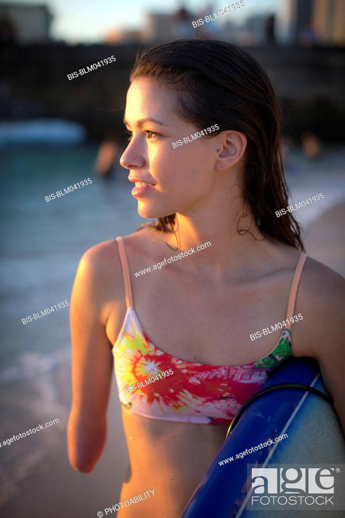 Stock Photo: Mixed race amputee carrying surfboard on beach.