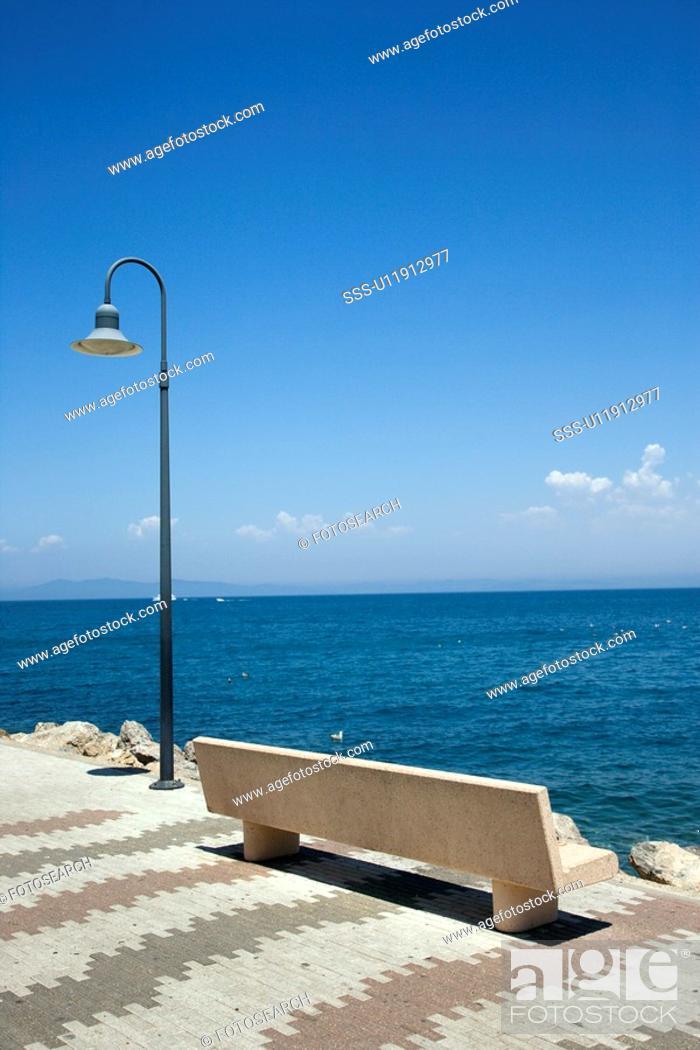 Stock Photo: Empty bench on dock overlooking water.