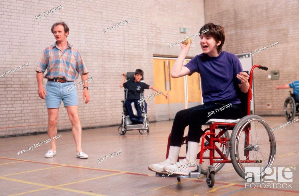 Stock Photo: Young girl with disability, who is wheelchair user, taking part in ball game in sports hall,.