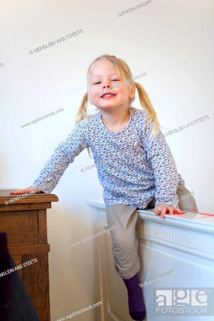 Stock Photo: Smiling girl climbing barrier indoors.