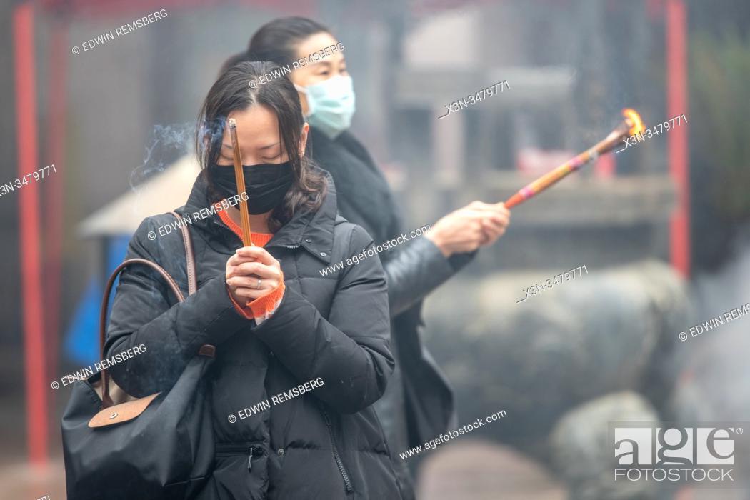 Stock Photo: Shanghai, China, 23rd Jan 2020, Women wearing masks pray with burning joss sticks, Edwin Remsberg.