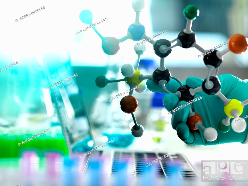 Stock Photo: Chemistry research, researcher designing a chemical formula using a molecular model.