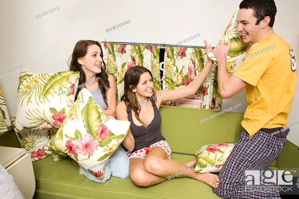 Stock Photo: Teenage friends having a pillow fight.