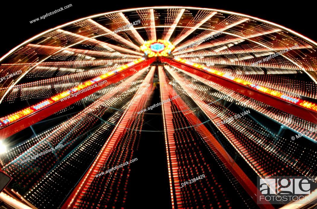Stock Photo: Ferris wheel glowing and spinning at nighttime; Locarno, Ticino, Switzerland.