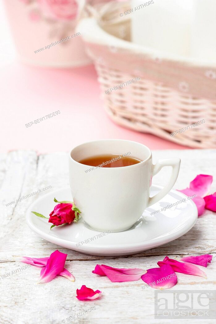 Stock Photo: Cup of tea decorated with rose petals in pink table setting.
