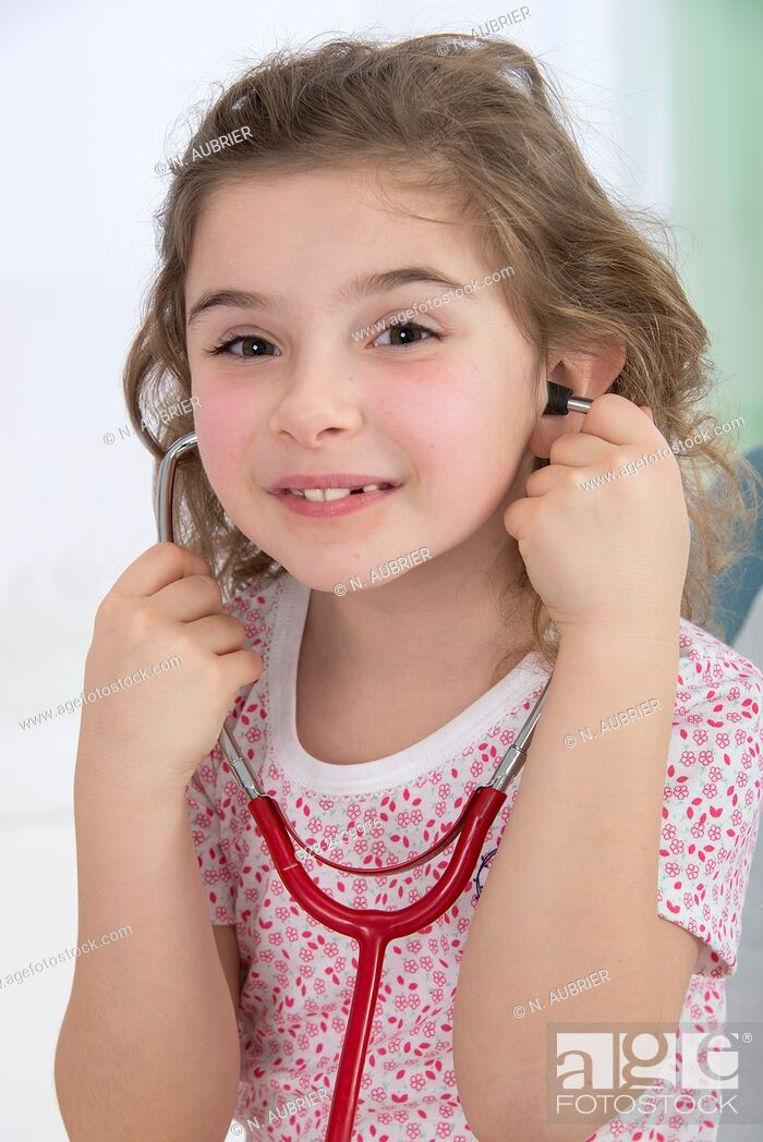 Stock Photo: Little smiling girl sitting on a medical couch and listening to her heart with a stethoscope.