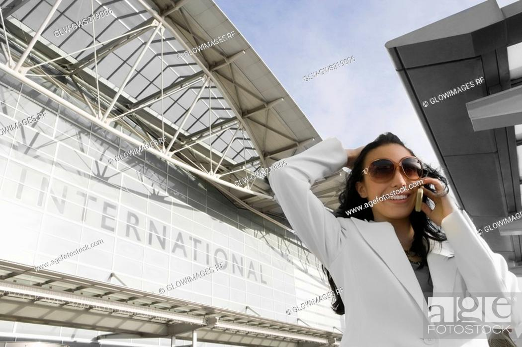 Stock Photo: Low angle view of a businesswoman talking on a mobile phone outside an airport.