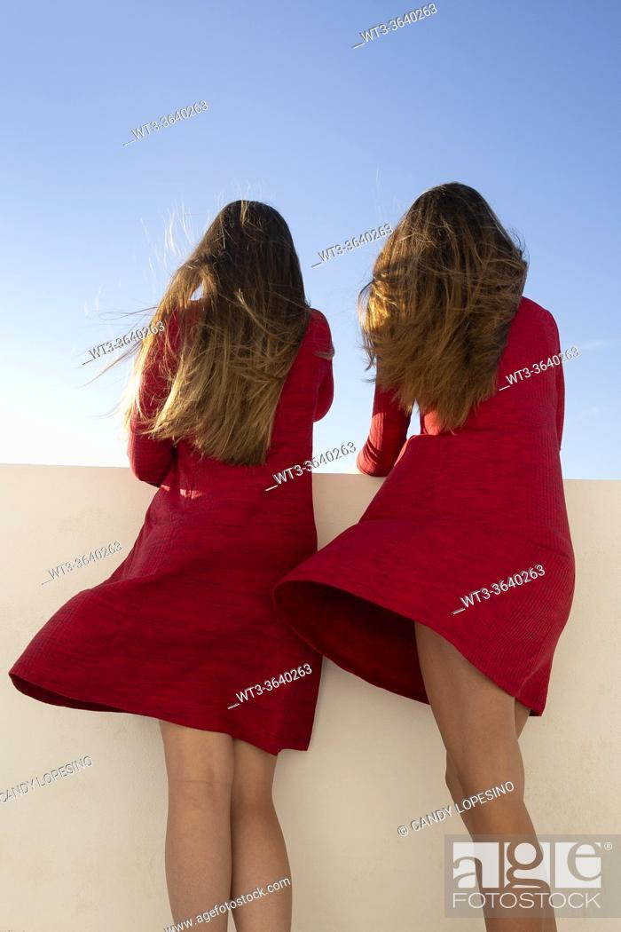 Stock Photo: Two young girls with red dresses and long blonde hair at the wind.
