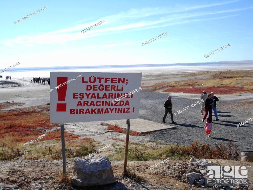 Stock Photo: turkey people walking near a warning plate.