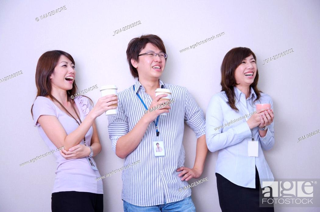 Stock Photo: Three colleagues holding drink together and looking away with smile.