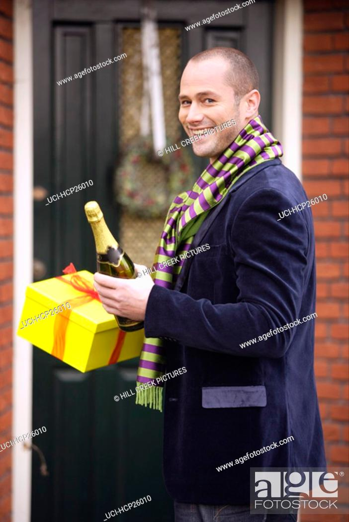 Stock Photo: Man holding gifts and champagne.