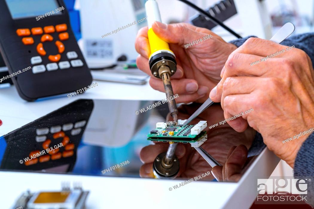 Stock Photo: Person soldering an electronic component.