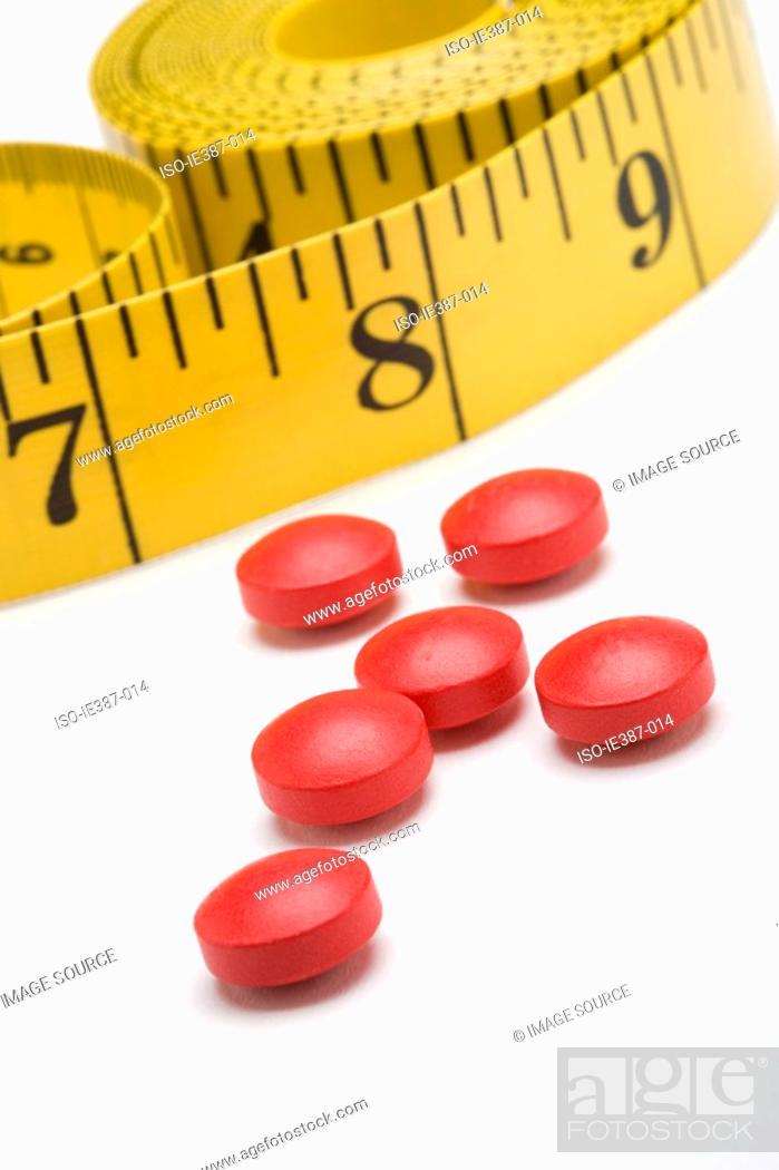 Stock Photo: Tape measure and diet pills.