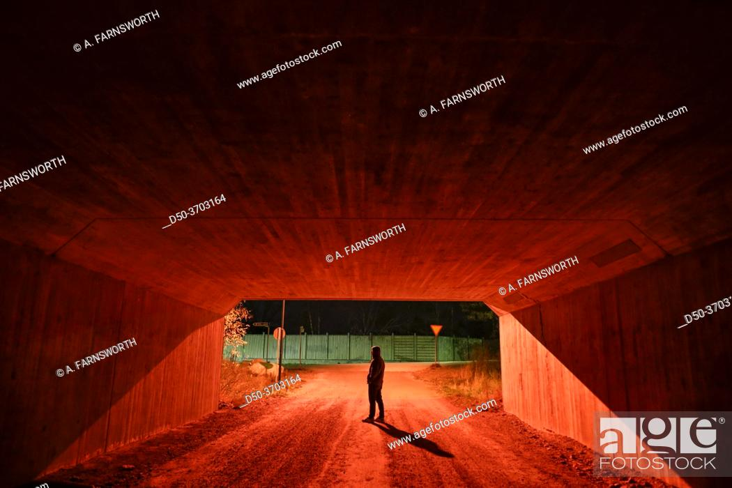 Stock Photo: Stockholm, Sweden A man walking in a red pedestrian tunnel at nght.