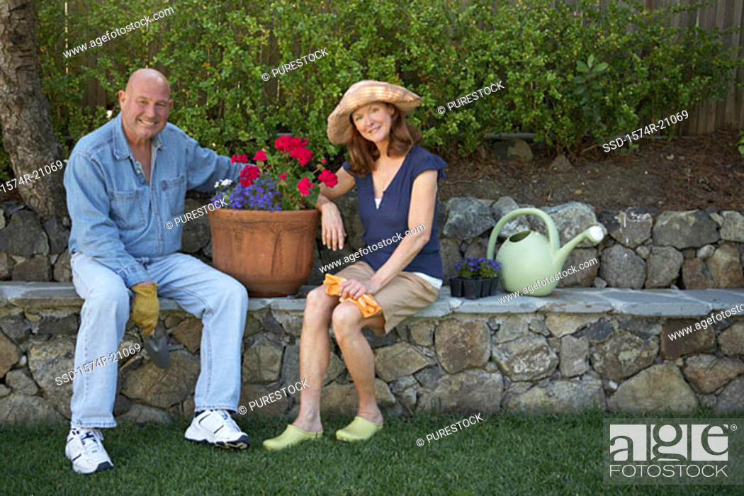 Stock Photo: Portrait of a mature couple sitting in a garden and smiling.